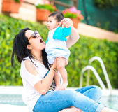 Young mother with her baby near the swimming pool. Mother playing with baby boy near the swimming pool on a sunny day royalty free stock images