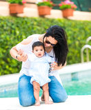 Young mother with her baby near the swimming pool. Smiling young mother playing with baby boy near the swimming pool on a sunny day royalty free stock photo