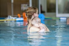 Young mother and her baby relaxing in a swimming pool Royalty Free Stock Images