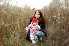 Young mother with her baby sitting in a grass. Young mother with her little baby in an overgrown grass Royalty Free Stock Photography