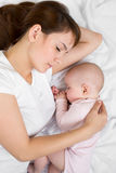 Young mother and her baby sleeping together Stock Photos