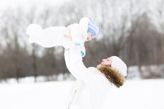 Young mother and her baby in the snow Royalty Free Stock Images
