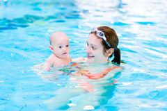 Young mother and her baby son in swimming pool. Young mother and her little baby son relaxing in a swimming pool Royalty Free Stock Photography