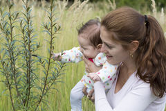 Young mother and her baby watching a caterpillar. Young biautiful mother and her baby watching a caterpillar royalty free stock images