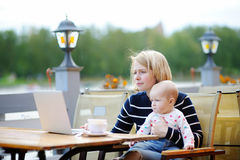 Young mother with her baby working or studying on laptop Stock Photography