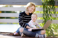 Young mother with her baby working or studying on laptop Stock Image