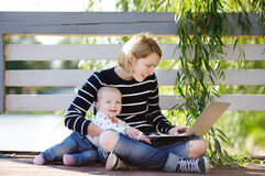 Young mother with her baby working or studying on laptop Stock Images