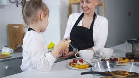 Young mother with her child cooking homemade pancakes together stock photography