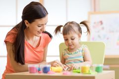 Young mother and her child daughter moulding together from plasticine Royalty Free Stock Image