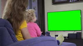 Young mother with her child girl watch tv and show finger. Green chroma screen stock video