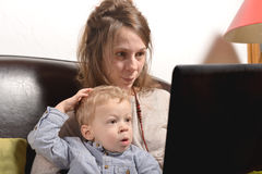 Young mother and her child looking at a laptop Stock Images