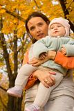 Young mother with her children in the park autumn Stock Photos