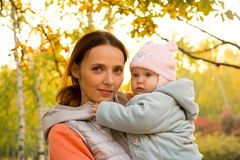 Young mother with her children in the park autumn Stock Photo
