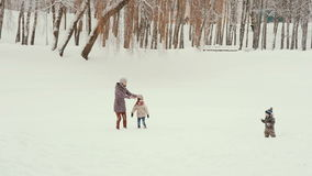 Young mother with her children playing and having fun in the snow stock footage