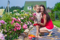 Young mother with her cute daughter near flowers Royalty Free Stock Images