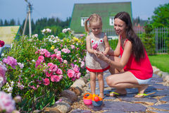 Young mother with her cute daughter near flowers Stock Photo