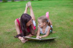 Young mother and her cute daughter reading book Royalty Free Stock Photography