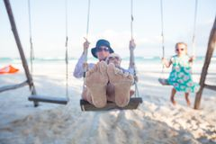 Young mother and her cute daughter swinging on a Stock Photos