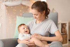 Young mother with her cute little baby sitting in armchair. At home Stock Photos