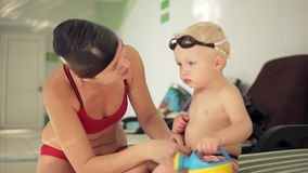 Young mother and her cute little blonde child sitting by the swimming pool and preparing for the swimming lesson. Happy. Mom talking to her child. Cute boy is stock footage