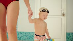 Young mother and her cute little blonde child walking near swimming pool. Happy mom spending time playing with her baby. Before the swimming lesson. Happy stock video footage