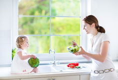 Young mother and her cute toddler daughter cooking royalty free stock images