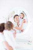 Young mother and her daughter applying make up Royalty Free Stock Image