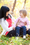 Young mother and her daughter on the autumv forest Royalty Free Stock Images