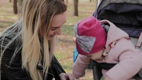 A young mother with her daughter in a baby carriage communicates. A young mother with her daughter in a baby carriage communicates stock footage