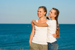 Young mother with her daughter on the beach. Stock Photo