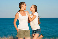 Young mother with her daughter on the beach. Stock Photos