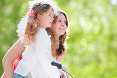 Young mother and her daughter on bicycle Royalty Free Stock Photos