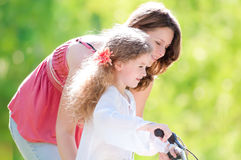 Young mother and her daughter on bicycle Royalty Free Stock Image