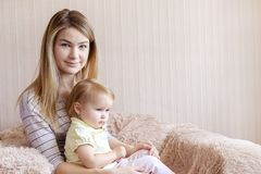 Young mother and her daughter child in armchair stock image