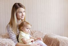 Young mother and her daughter child in armchair stock photo