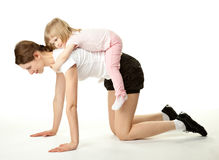 Young mother and her daughter doing sport Stock Photos