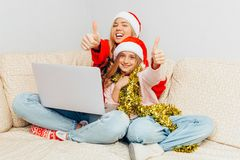 Young mother and her daughter dressed in Santa Claus hats using stock images