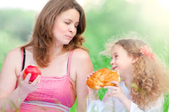 Young mother and her daughter eating Royalty Free Stock Image