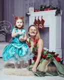 Young mother and her daughter in fancy Christmas costumes. Young mother and her daughter in fancy costumes in Christmas decorations Stock Image