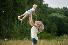 Young mother with her daughter in the field. Mom throws up the baby. Happy emotions. Summer day stock photo