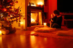 Young mother and her daughter by a fireplace Stock Photos