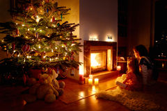 Young mother and her daughter by a fireplace Stock Images