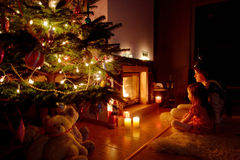 Young mother and her daughter by a fireplace Royalty Free Stock Photos