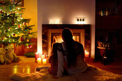 Young mother and her daughter by a fireplace Royalty Free Stock Photo