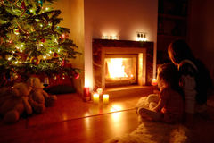 Young mother and her daughter by a fireplace Stock Photo
