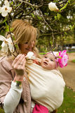 Young mother with her daughter in a garden. Beautiful young mother with her baby daughter in a garden at spring stock photo