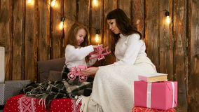 Young mother and her daughter happily playing with toys on Christmas eve stock video