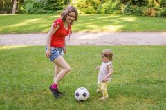 Young mother and her daughter have a fun. Woman and child are playing with ball in park Royalty Free Stock Images