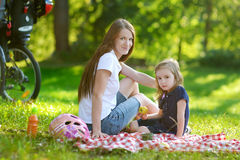 Young mother and her daughter having a picnic Royalty Free Stock Photo