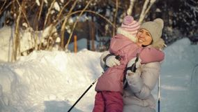 Mom and daughter hug after nordic walking in the suburbs in winter. stock video
